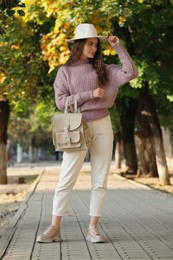 Young woman with stylish beige backpack on city street