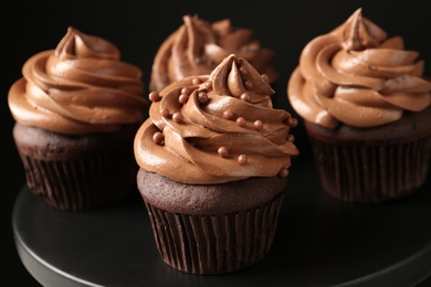 Delicious chocolate cupcakes with cream and beads on black table, closeup
