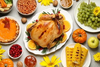 Traditional Thanksgiving day feast with delicious cooked turkey and other seasonal dishes served on grey table, flat lay