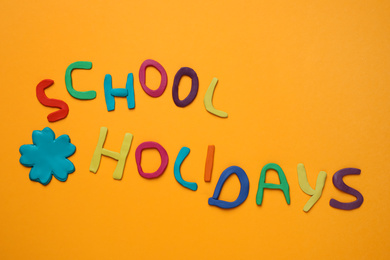 Phrase School Holidays made of modeling clay on orange background, top view