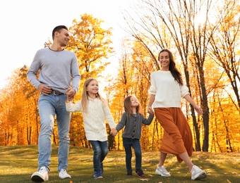 Happy family with little daughters walking in autumn park