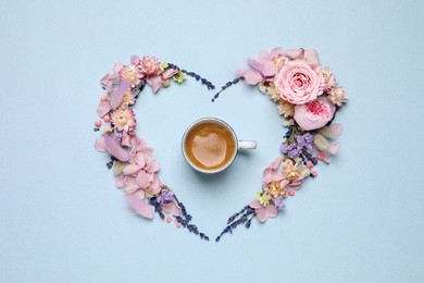 Beautiful heart shaped floral composition with cup of coffee on light background, flat lay