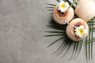 Fresh coconuts with drinking straws and flowers on grey table, flat lay. Space for text