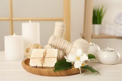 Composition with beautiful jasmine flowers and burning candles on white wooden table indoors