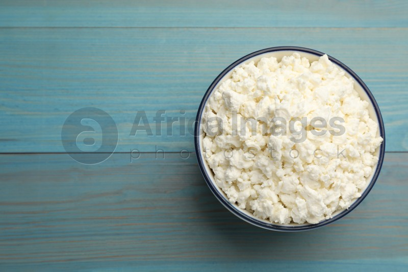 Delicious fresh cottage cheese on blue wooden table, top view. Space for text