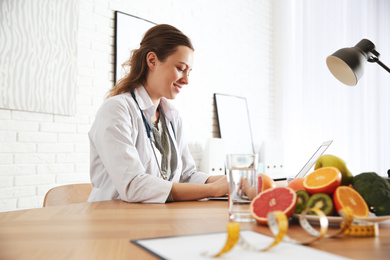 Nutritionist working with laptop at desk in office