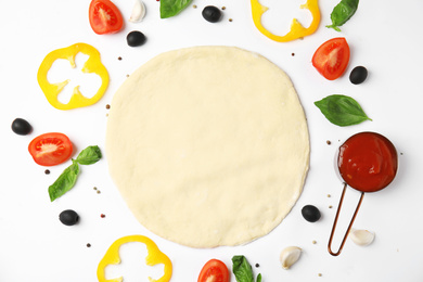 Flat lay composition with dough and fresh ingredients for pizza on white background