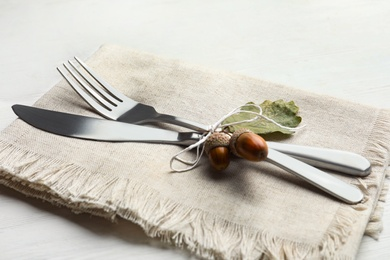 Cutlery with napkin, acorns and napkin on white wooden background, closeup. Table setting elements