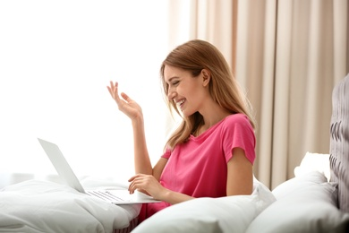 Young woman using modern laptop in bedroom