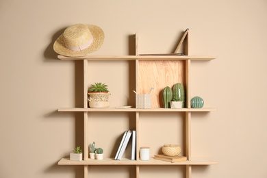 Wooden shelves with different decorative elements on beige wall
