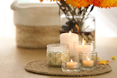 Beautiful burning candles, bag and flowers on table at home