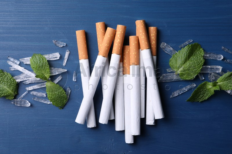 Cigarettes, menthol crystals and mint leaves on blue wooden table, flat lay