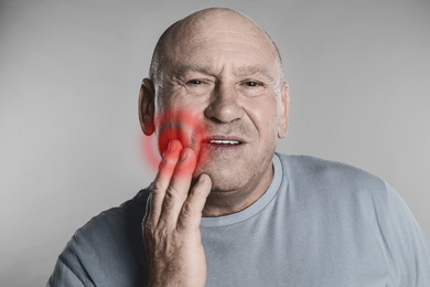 Senior man suffering from toothache on grey background