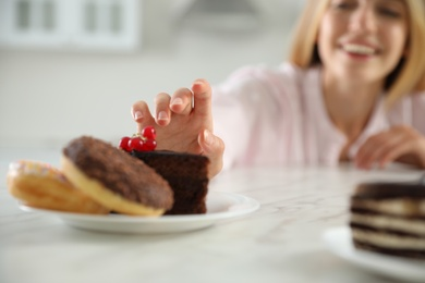 Concept of choice between healthy and junk food. Woman with sweets at white table in kitchen, focus on hand