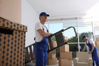 Moving service employees with ladder and cardboard boxes in room