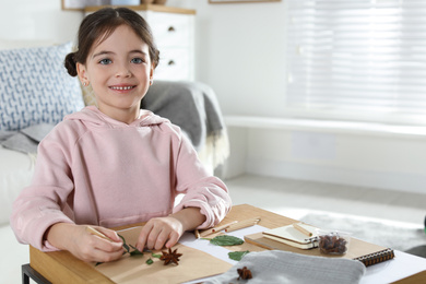 Little girl working with natural materials at table indoors, space for text. Creative hobby