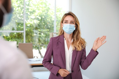 Woman in protective mask saying hello in office. Keeping social distance during coronavirus pandemic