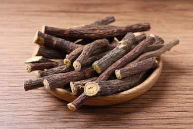 Dried sticks of liquorice root on wooden table, closeup