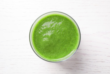 Delicious fresh green juice on white wooden table, top view