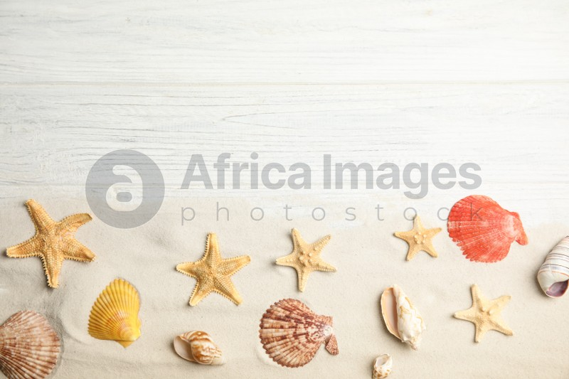 Beautiful sea stars, shells and sand on white wooden background, flat lay. Space for text