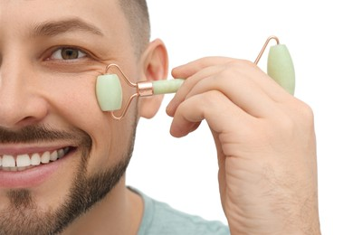 Man using nephrite facial roller on white background, closeup