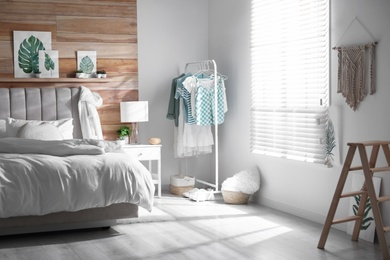 Stylish bedroom interior with clothing rack and large window