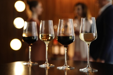 Glasses of different wines on table against blurred background