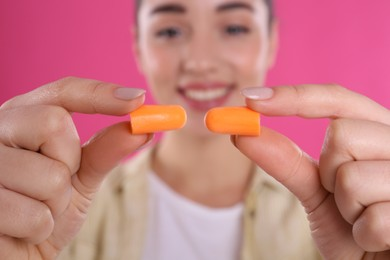 Young woman with foam ear plugs against pink background, focus on hands