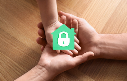 Home security concept. Family holding house indoors, closeup