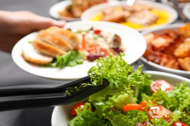 Woman taking food from buffet table, closeup
