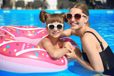 Mother and daughter in swimming pool on sunny day. Family vacation