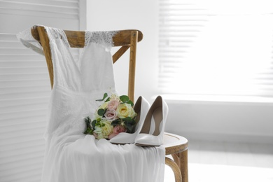 White high heel shoes, flowers and wedding dress on wooden chair indoors. Space for text