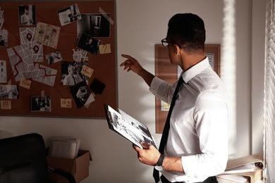 Detective with clipboard working in his office