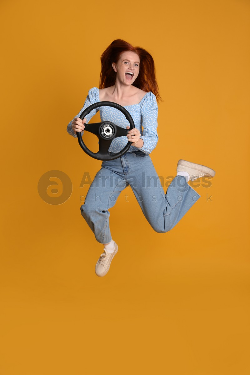 Excited young woman jumping with steering wheel on yellow background