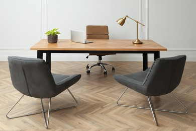 Director's office with large wooden table and comfortable armchairs. Interior design