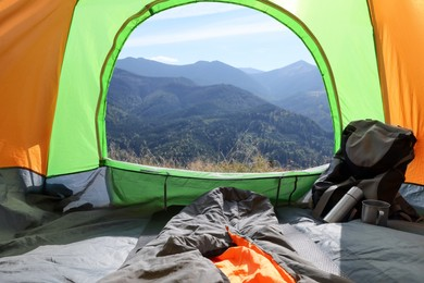 Camping tent with sleeping bag and backpack in mountains, view from inside