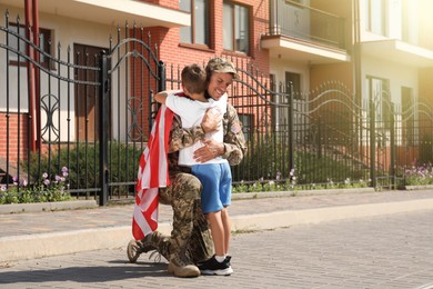 Soldier with flag of USA and his little son hugging outdoors