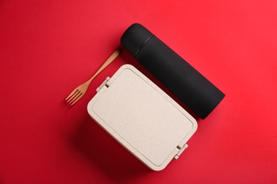 Thermos and lunch box with fork on red background, flat lay