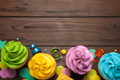 Flat lay composition with colorful birthday cupcakes on wooden table. Space for text