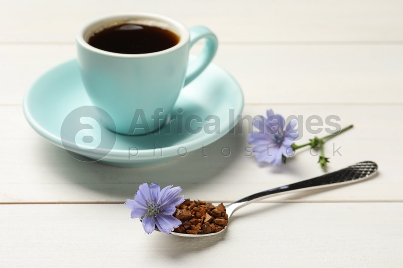 Spoon of chicory granules with flower on white wooden table