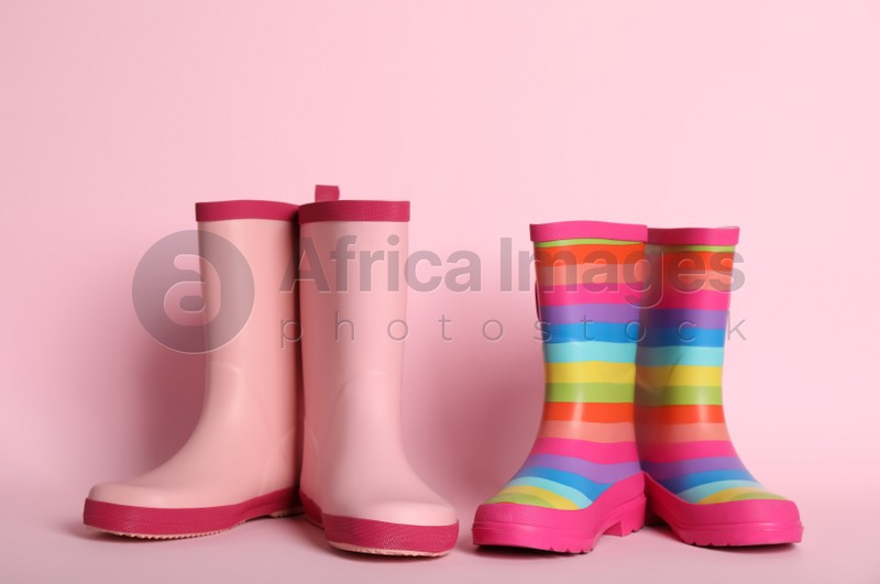 Two pairs of rubber boots on pink background