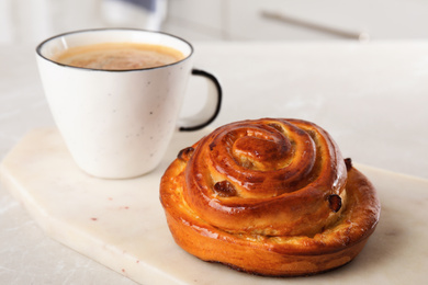Delicious bun and coffee on light table. Sweet pastries