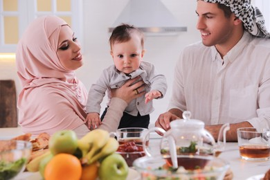 Happy Muslim family with little son at served table in kitchen