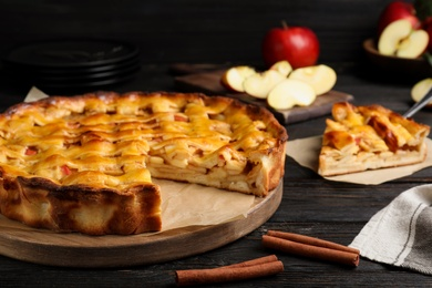 Traditional apple pie on black wooden table