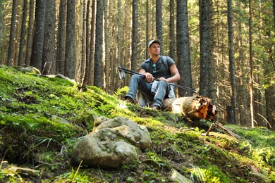 Hiker with trekking poles resting in mountain forest