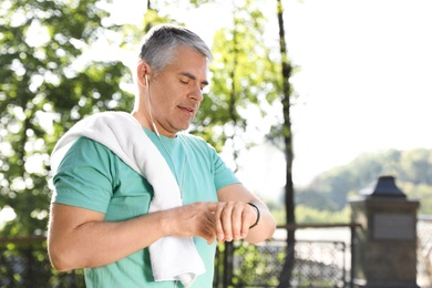 Handsome mature man looking at fitness tracker in park. Healthy lifestyle