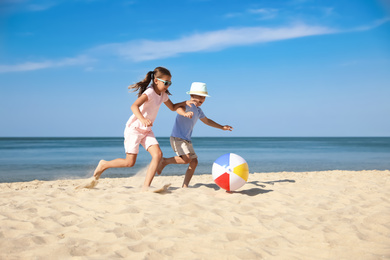Cute little children playing with inflatable ball on sandy beach