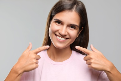 Young woman with healthy teeth on light background. Cosmetic dentistry
