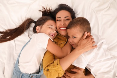 Happy mother with her children on bed, top view