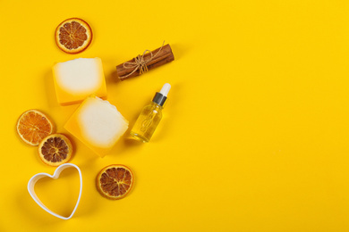 Flat lay composition with natural handmade soap and ingredients on yellow background. Space for text
